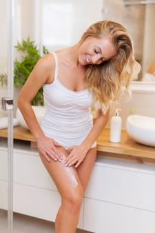 Mulher loira aplicando loção corporal nas pernas