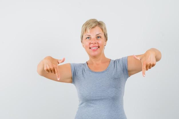 Mulher loira apontando para baixo com o dedo indicador em uma camiseta azul claro e parecendo alegre. vista frontal.