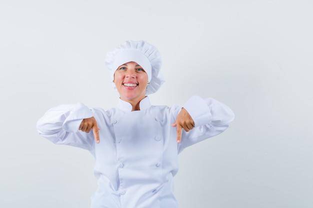 Mulher loira apontando para baixo com o dedo indicador em uniforme de cozinheira branco e bonita