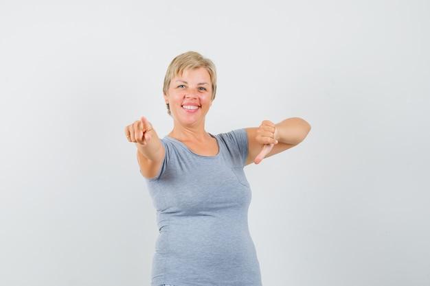 Mulher loira apontando para baixo em uma camiseta azul clara e parecendo feliz, vista frontal.