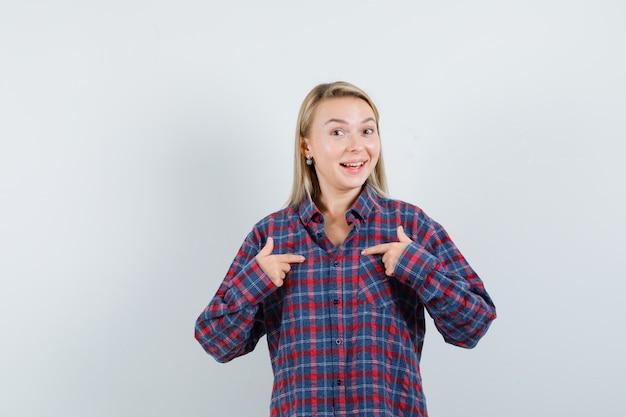 Mulher loira apontando para si mesma com os dedos indicadores em uma camisa xadrez e parecendo animada. vista frontal.
