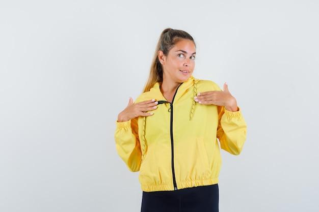 Mulher loira apontando para si mesma com os dedos indicadores em uma jaqueta de bombardeiro amarela e calças pretas e parecendo feliz