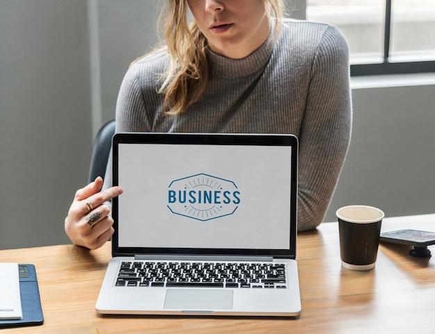 Mulher loira, apontando para uma tela de laptop