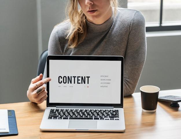 Mulher loira apontando para uma tela de laptop
