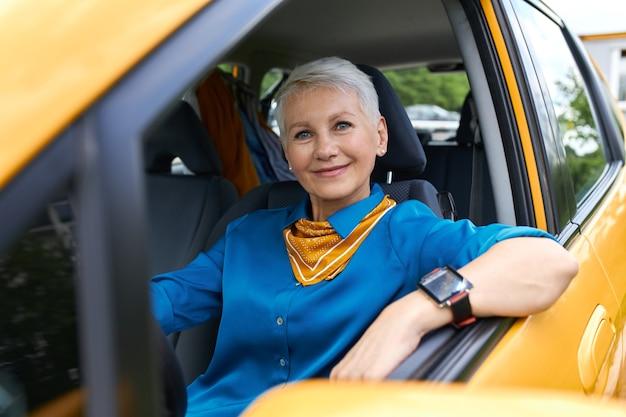 Mulher loira aposentada atraente e bem-sucedida, vestindo camisa azul e relógio de pulso, sentada confortavelmente em seu novo carro amarelo, apoiando o cotovelo na janela aberta, com uma expressão facial feliz e confiante
