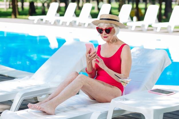 Mulher loira aposentada segurando um smartphone rosa e descansando sentada na sala de perseguição