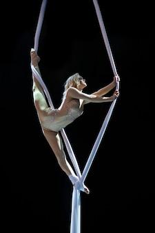 Mulher loira artista aérea com sedas aéreas brancas isoladas no fundo preto