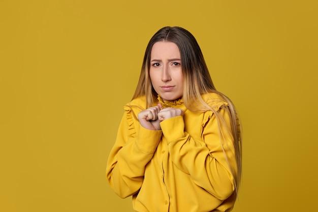 Mulher loira assustada em fundo amarelo. emoções humanas, expressões faciais.