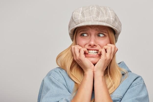 Mulher loira assustada olha de lado assustada com medo batendo os dentes de medo