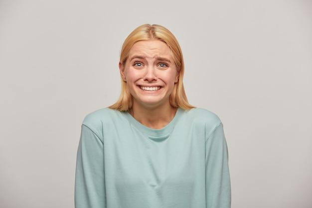 Mulher loira assustada parece assustada com medo batendo os dentes de medo, ver algo inesperado assustador na frente