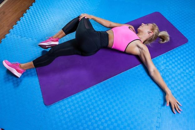 Mulher loira ativa na esteira fazendo exercícios de aquecimento. mulher apta deita-se no tapete de ioga e pratica o alongamento das pernas e de todo o corpo. estilo de vida saudável, conceito de fitness