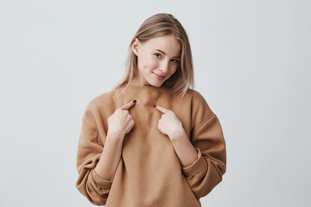 Mulher loira atraente bonita sorrindo, apontando com o dedo indicador para si mesma, vestida de camisola bege de manga comprida, expressando sentimentos e emoções positivas.