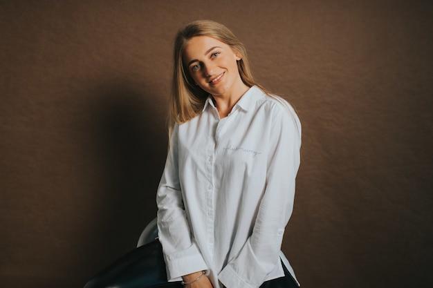 Mulher loira atraente, branca, com uma camisa branca e posando em um fundo marrom