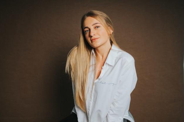 Mulher loira atraente, branca com uma camisa branca, posando em um marrom