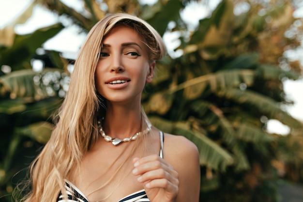 Mulher loira atraente bronzeada com colar de pérolas e roupa listrada sorri e desvia o olhar