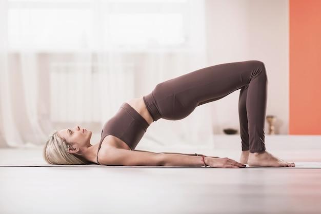Mulher loira atraente com legging esportiva bege e regata praticando ioga fazendo exercícios de ponte de glúteos dvi pada pithasana pose