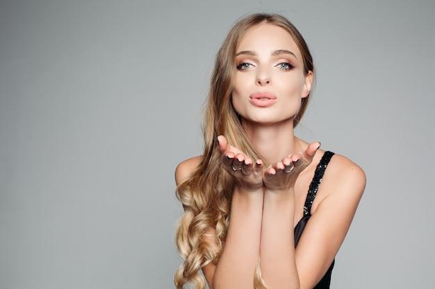 Mulher loira atraente com maquiagem profissional, vestindo um blous prata elegante