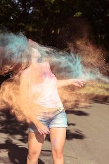 Mulher loira atraente com vento no cabelo se divertindo com tinta holi seca explosiva