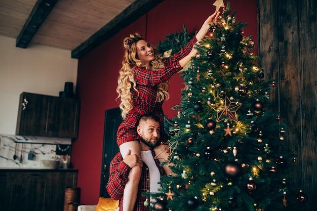 Mulher loira atraente de pijama vermelho, colocando a estrela de natal na árvore de natal. férias juntos.