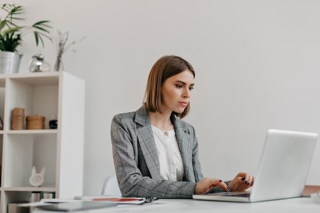 Mulher loira atraente digitando carta no laptop em seu local de trabalho. retrato de senhora de casaco elegante em escritório brilhante.
