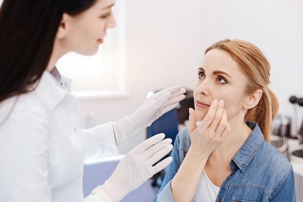 Mulher loira atraente e agradável olhando para o médico e apontando para a bochecha dela enquanto explica seus desejos