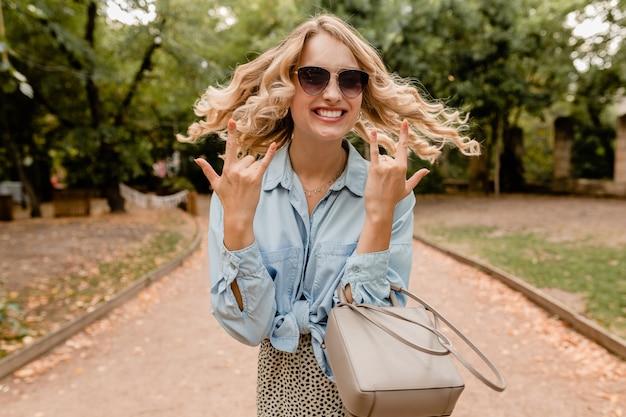 Mulher loira atraente e cândida andando no parque com roupa elegante, óculos escuros elegantes e bolsa