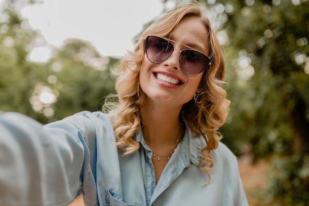 Mulher loira atraente e sorridente andando no parque com roupa de verão tirando foto de selfie no telefone