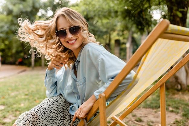 Mulher loira atraente e sorridente sentada em uma espreguiçadeira com roupa de verão