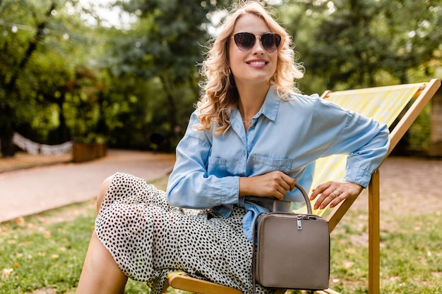 Mulher loira atraente e sorridente sentada em uma espreguiçadeira com roupa elegante