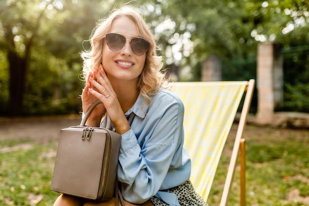 Mulher loira atraente e sorridente, sentada em uma espreguiçadeira com uma camisa azul com roupa de verão, usando elegantes óculos escuros, segurando uma bolsa, acessórios de moda de rua
