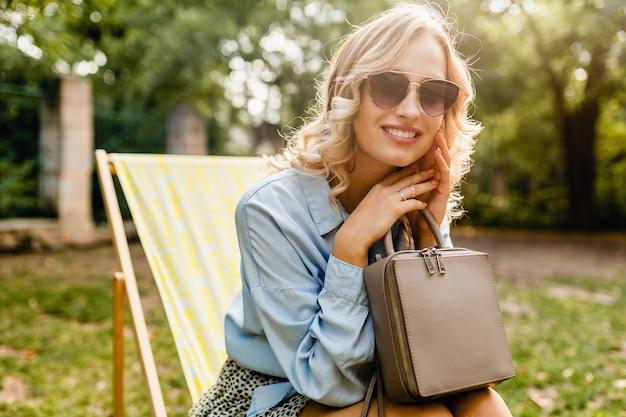 Mulher loira atraente e sorridente, sentada em uma espreguiçadeira, com uma camisa azul elegante, usando óculos escuros elegantes, segurando uma bolsa, acessórios de estilo outono de moda de rua