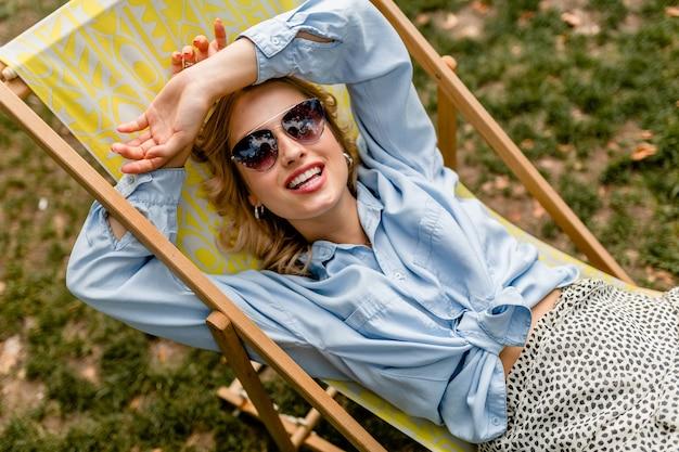 Mulher loira atraente e sorridente sentada relaxada em uma cadeira de praia em uma roupa elegante