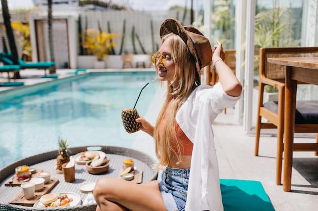 Mulher loira atraente em óculos de sol amarelos, passando um tempo perto da piscina com um saboroso coquetel de abacaxi. uma turista feminina sonhadora comendo frutas durante a sessão de fotos no resort.