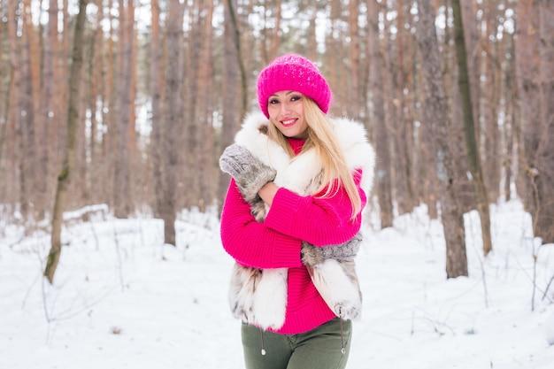 Mulher loira atraente em pé com um chapéu rosa e suéteres
