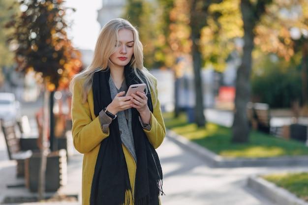 Mulher loira atraente emocional fofa com casaco e smartphone caminhando pela cidade