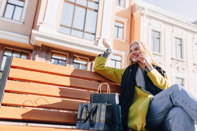 Mulher loira atraente feliz fofa com pacotes na rua em tempo ensolarado
