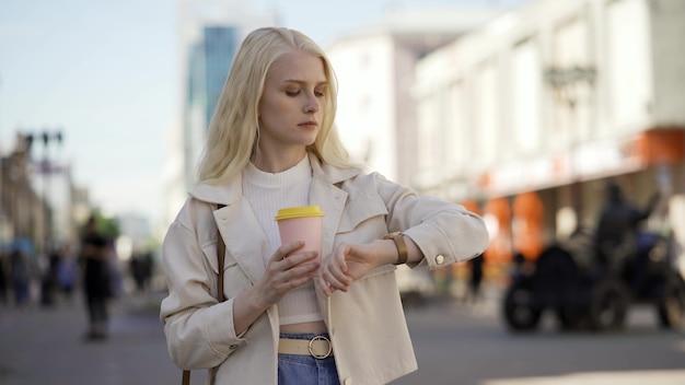 Mulher loira atraente fica na rua e espera por alguém. ela olha para o relógio e bebe o café que comprou no caminho. cansada espera, estar atrasado para uma reunião. 4k uhd