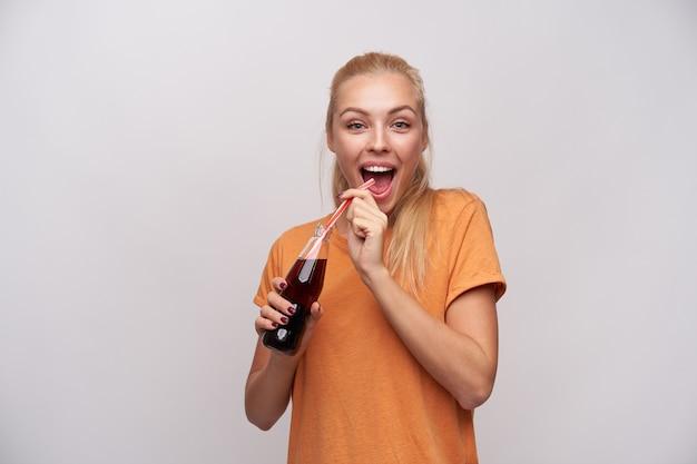 Mulher loira atraente jovem alegre com penteado de rabo de cavalo, olhando alegremente para a câmera com a boca aberta e mantendo a garrafa de refrigerante nas mãos levantadas, isolada sobre fundo branco