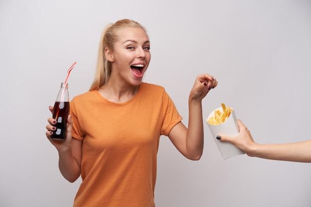 Mulher loira atraente jovem alegre com penteado de rabo de cavalo, segurando a garrafa com canudo na mão levantada e pegando batatas fritas com um largo sorriso feliz, isolado sobre fundo branco