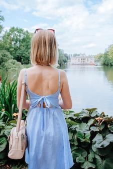 Mulher loira atraente olhando para o palácio e o lago no parque em varsóvia