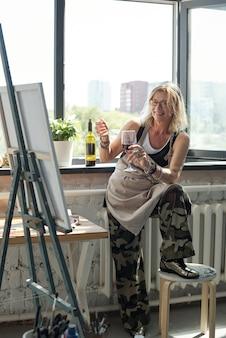 Mulher loira atraente positiva de avental bebendo vinho e olhando para a própria foto