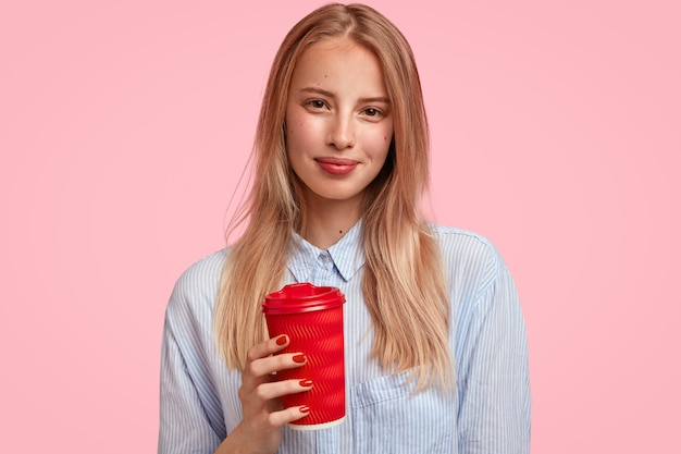 Mulher loira atraente segura bebida quente em copo de papel descartável, veste uma camisa elegante, fica contra a parede rosa, tem uma pausa depois de ter palestras. conceito de pessoas e tempo livre