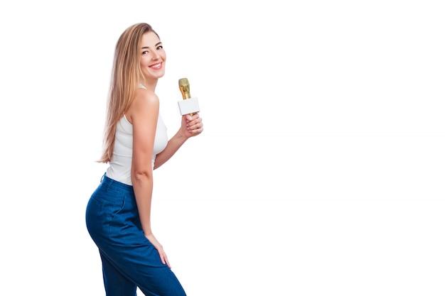 Mulher loira atraente segurando o microfone e o sorriso.