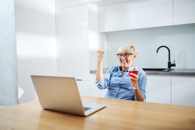 Mulher loira atraente sênior, sentado à mesa de jantar, bebendo vinho, olhando para o laptop e torcendo pela conquista