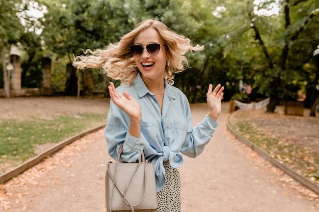 Mulher loira atraente sorridente acenando cabelo comprido e se divertindo andando no parque com roupa de verão