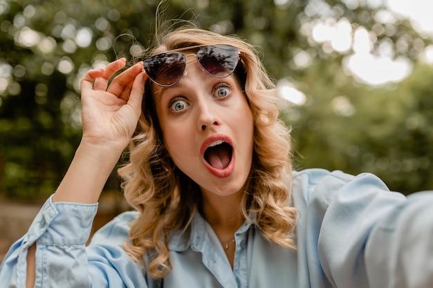 Mulher loira atraente surpresa e engraçada com roupa de verão tirando foto de selfie no telefone