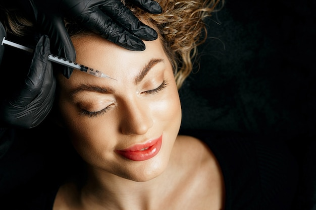Mulher loira atraente tendo injeção de preenchimento na testa. conceito de cosmetologia. copyspace