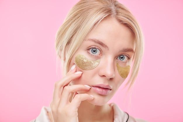 Mulher loira atraente tocando seu rosto durante o procedimento de cuidados com a pele para a área sob os olhos contra a parede rosa