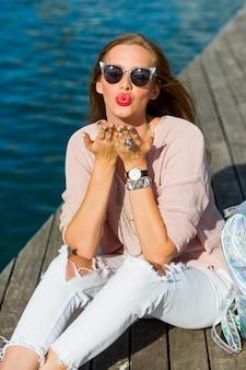 Mulher loira atraente turista posando ao ar livre em dia de sol.