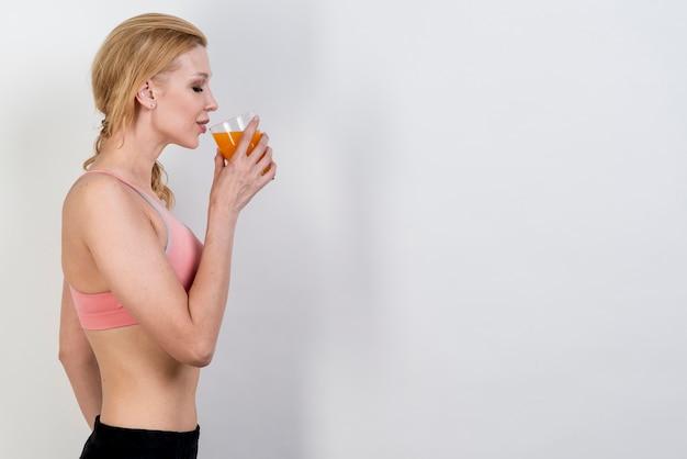 Mulher loira bebendo suco de laranja